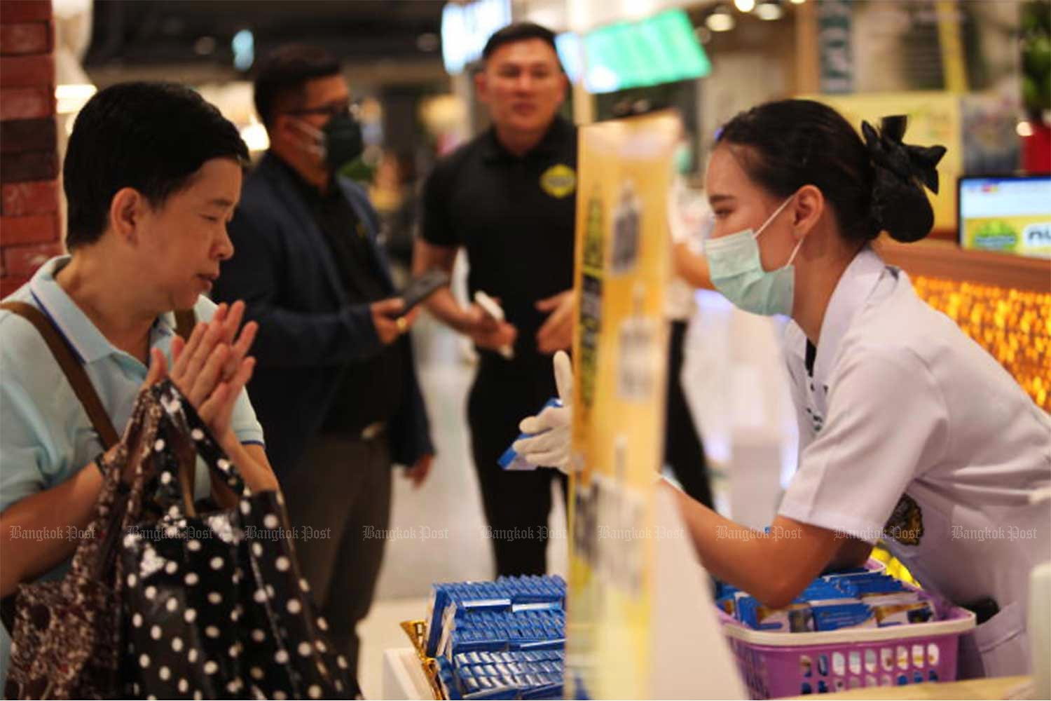 An employee of Tumrubthai herbal shop hands out fah talai jone herbal medicine to people at CentralWorld shopping mall on March 6 last year. Each person is given one pack of the drug for free. (Photo by Apichart Jinakul)