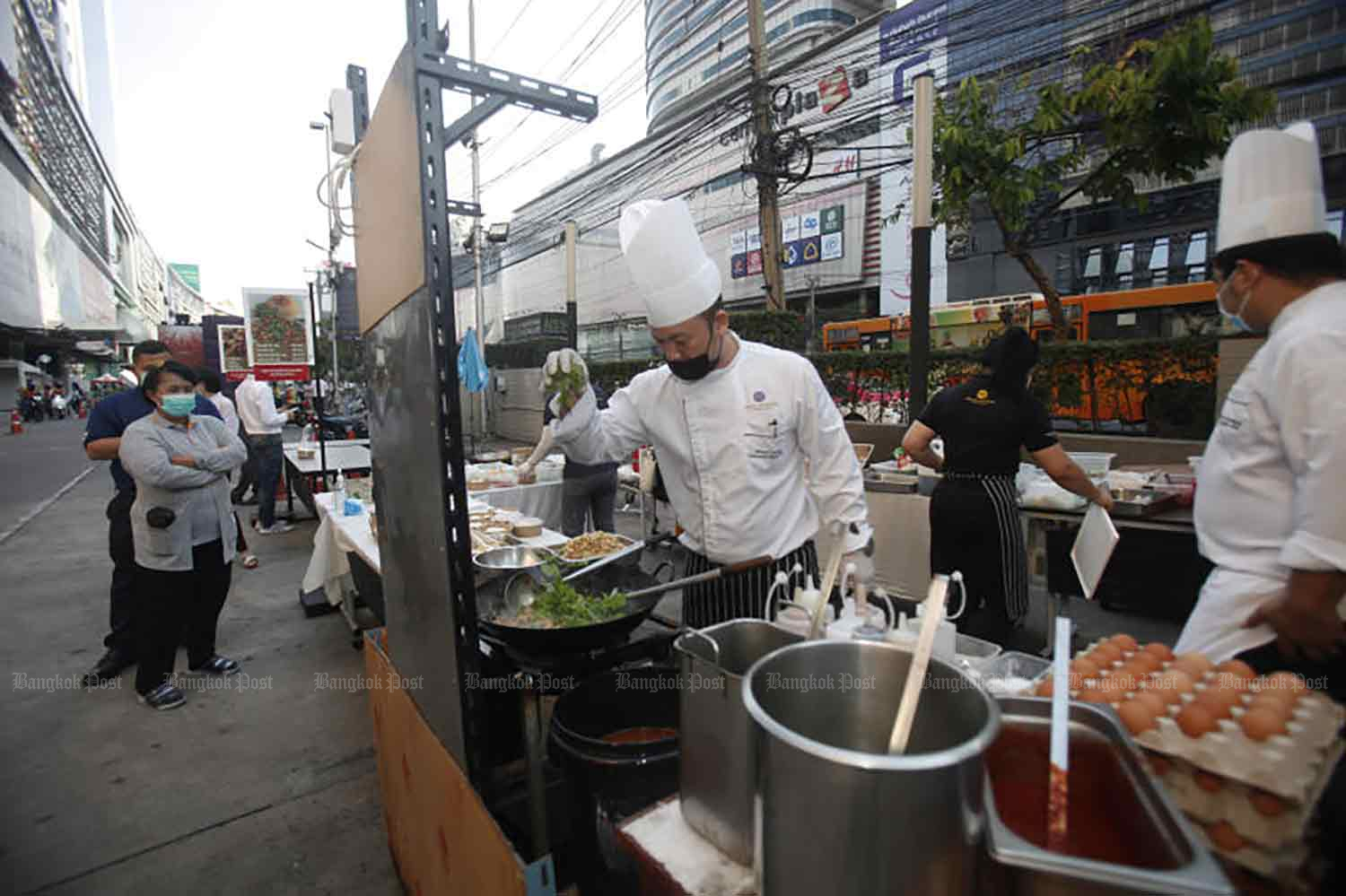 With most hotels empty of guests, chefs from the Grand Mercure Hotel on Ratchadaphisek Road were out on the street preparing food for sale to passers-by, in Bangkok on Friday. (Photo: Nutthawat Wicheanbut)