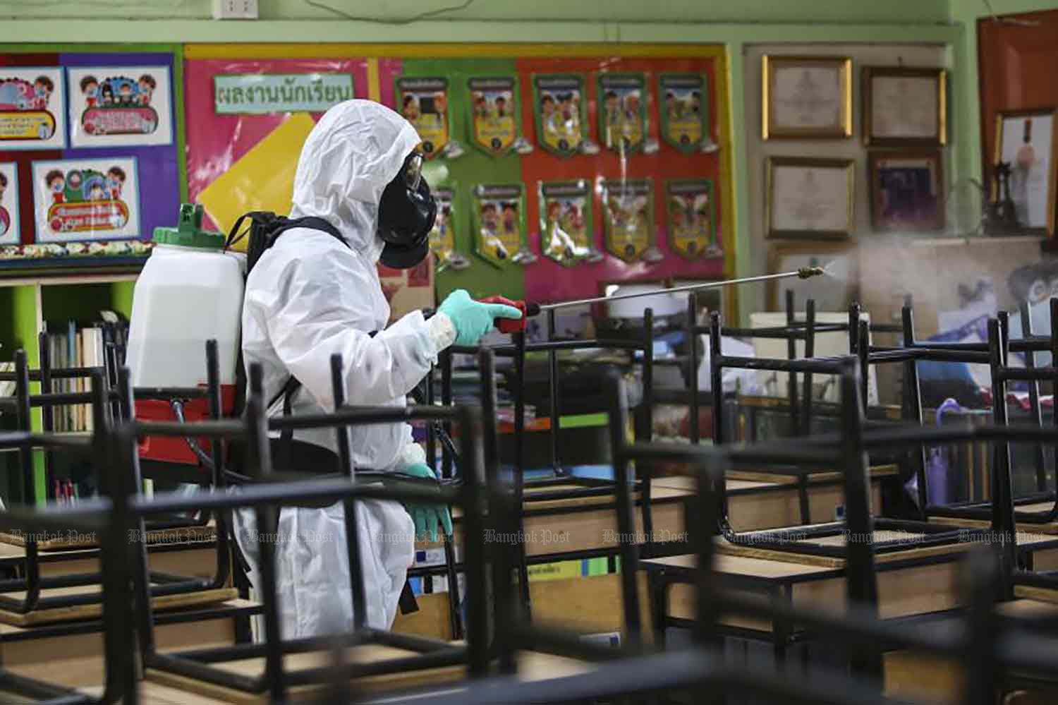 A disease control worker sprays disinfectant at Prachaniwet School in Chatuchak district, Bangkok, on Friday. Schools will reopen on Monday when many businesses and other activities will also resume to varying degree. (Photo: Pattarapong Chatpatarasill)