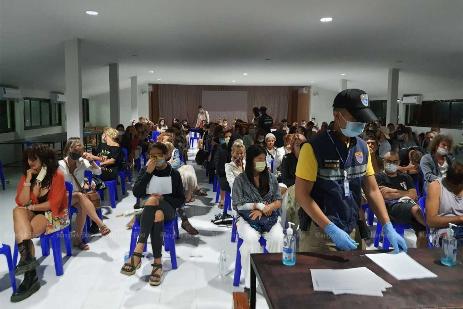 The 111 people arrested partying in breach of Covid-19 controls at the Three Sixty Bar on Koh Phangan island on Tuesday night were seated well apart when taken to the district office. (Photo: Surat Thani immigration/ Supapong Chaolan)