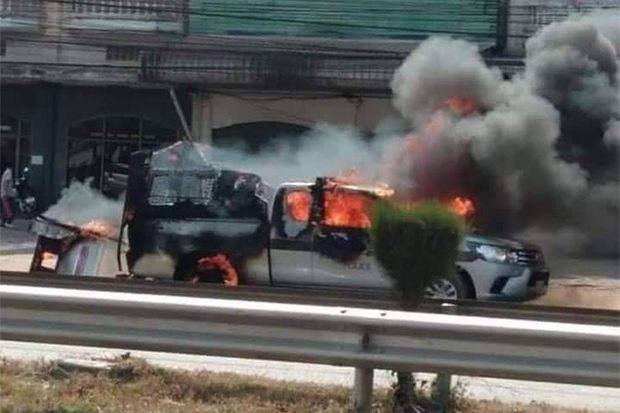 Flames consume a police pickup truck that was set ablaze while it was carrying four suspects to the provincial court in Udon Thani on Friday. @fm91trafficpro Twitter account)
