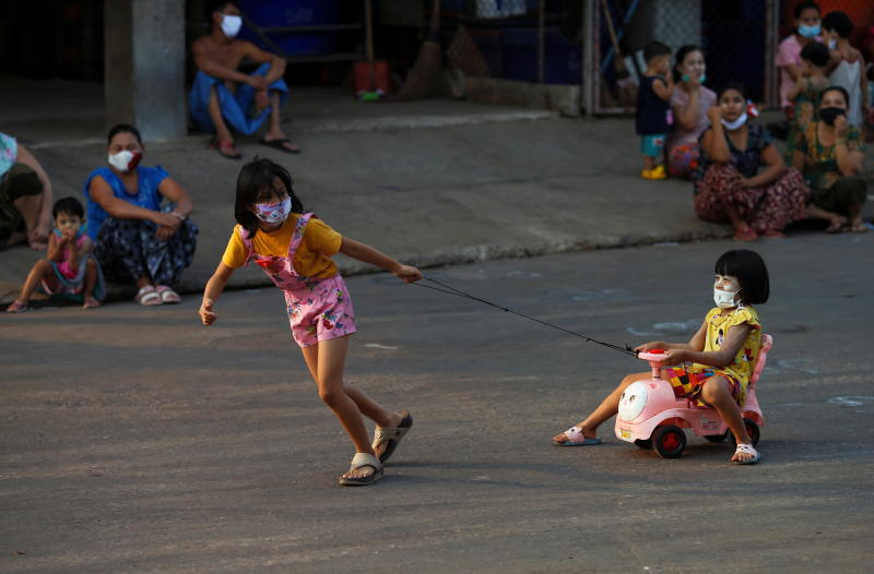 A girl pulls a cart as Myanmar migrant worker families pass their time under barricade lockdown at the Central Shrimp Market in Samut Sakhon's Muang district on Friday. (Reuters photo)