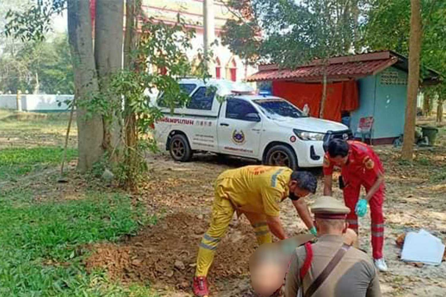 Rescue workers and a police officer inspect the body of a man killed by a wild elephant in the compound of Wat Anan in Hua Hin on Saturday. (Photo from @phetkasemthailand charity foundation Facebook page)