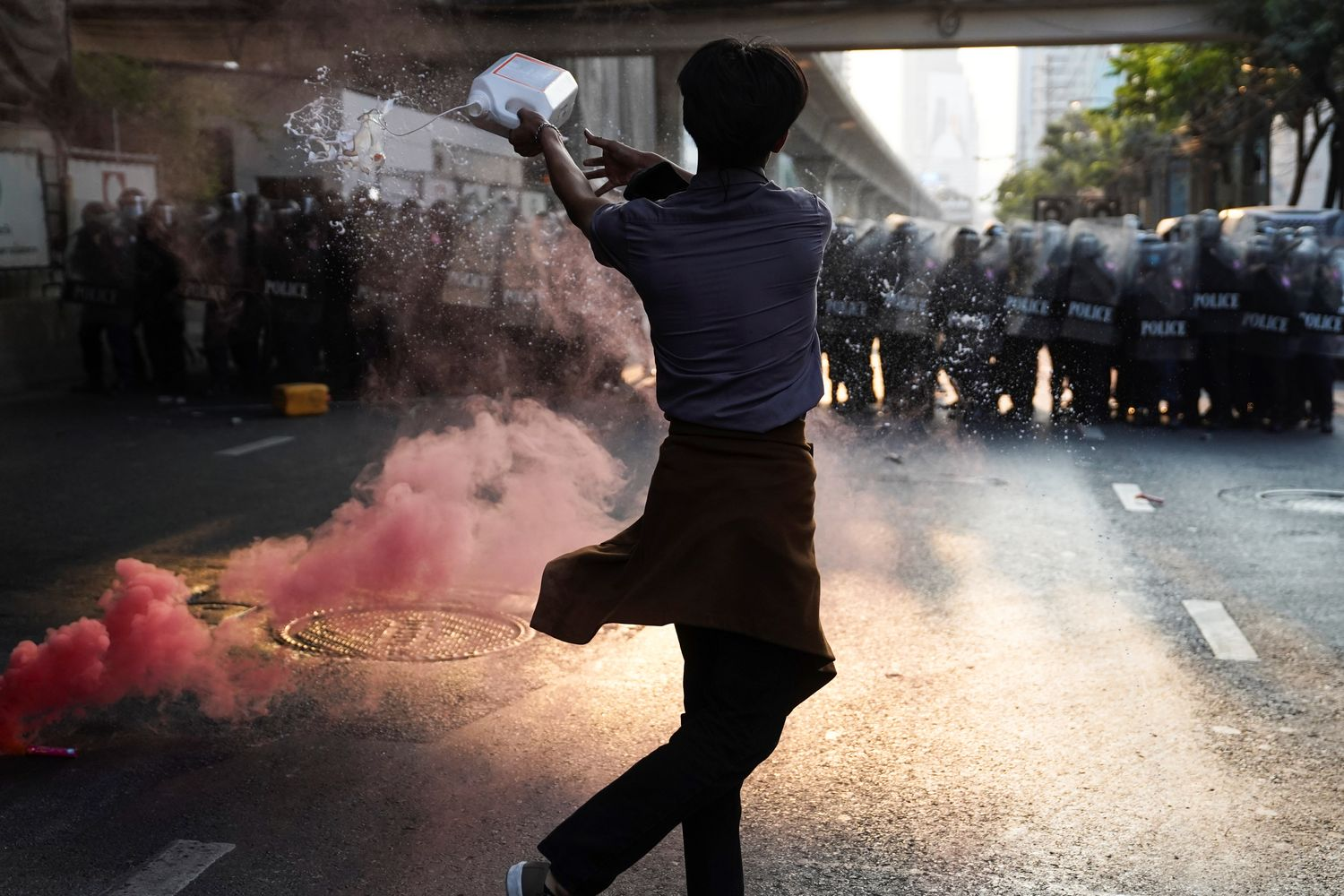 Anti-Thai government protester throws a liquid during a clash with riot police after protesters showed up at a rally for Myanmar's democracy outside the embassy in Bangkok on Monday. (Reuters photo)