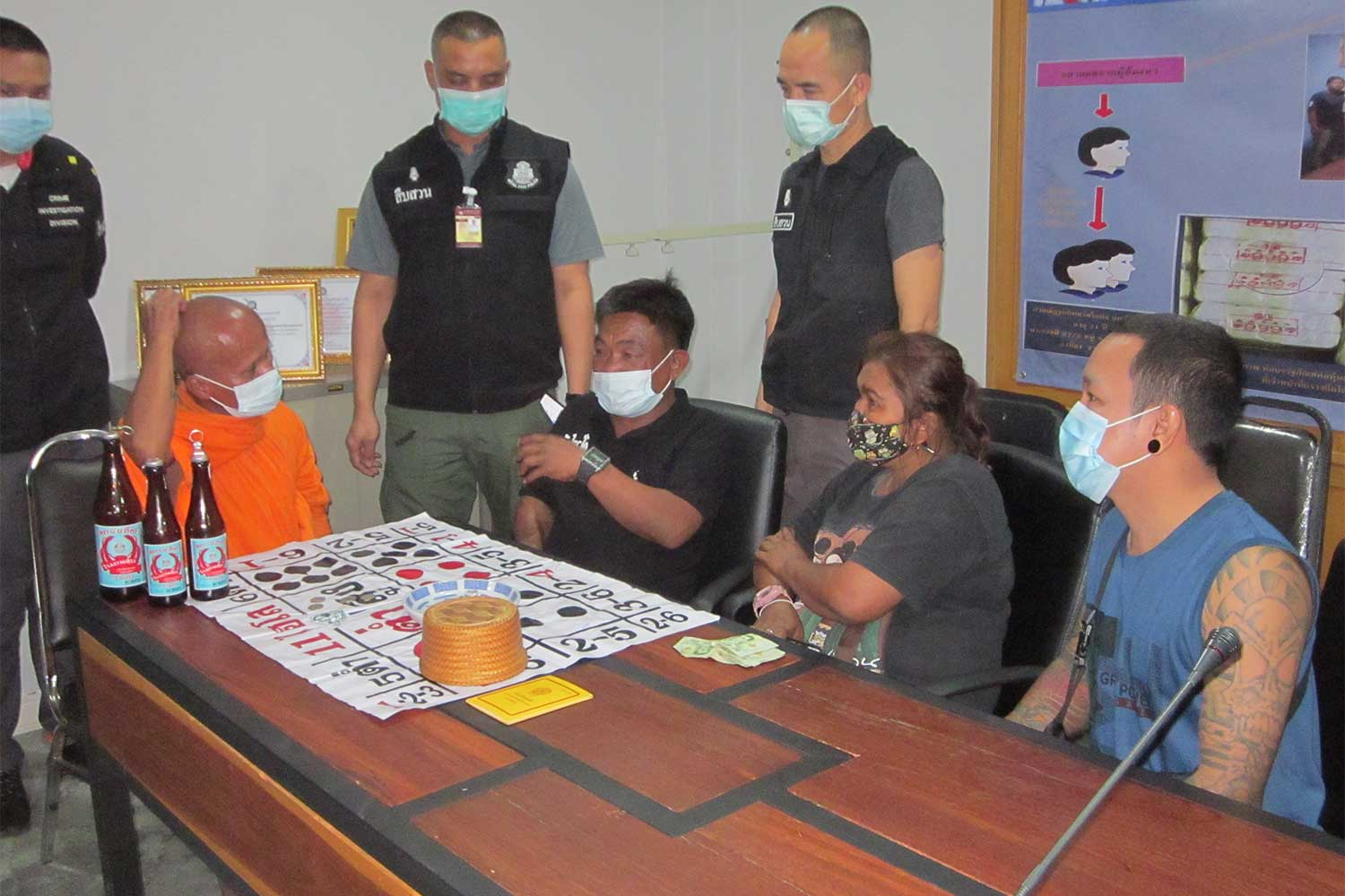 Phra Mao, 53, and three other gamblers, all seated, at Muang police station in Nakhon Sawan after the police raid  on Monday night, along with the three seized bottles of alcohol and a high-low dice game. (Photo: Chalit Pumruang)