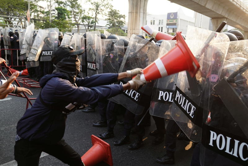 An anti-Thai government protester wields a traffic cone at riot police during a clash at a rally for Myanmar's democracy outside the Myanmar embassy, in Bangkok on Monday. (Reuters photo)