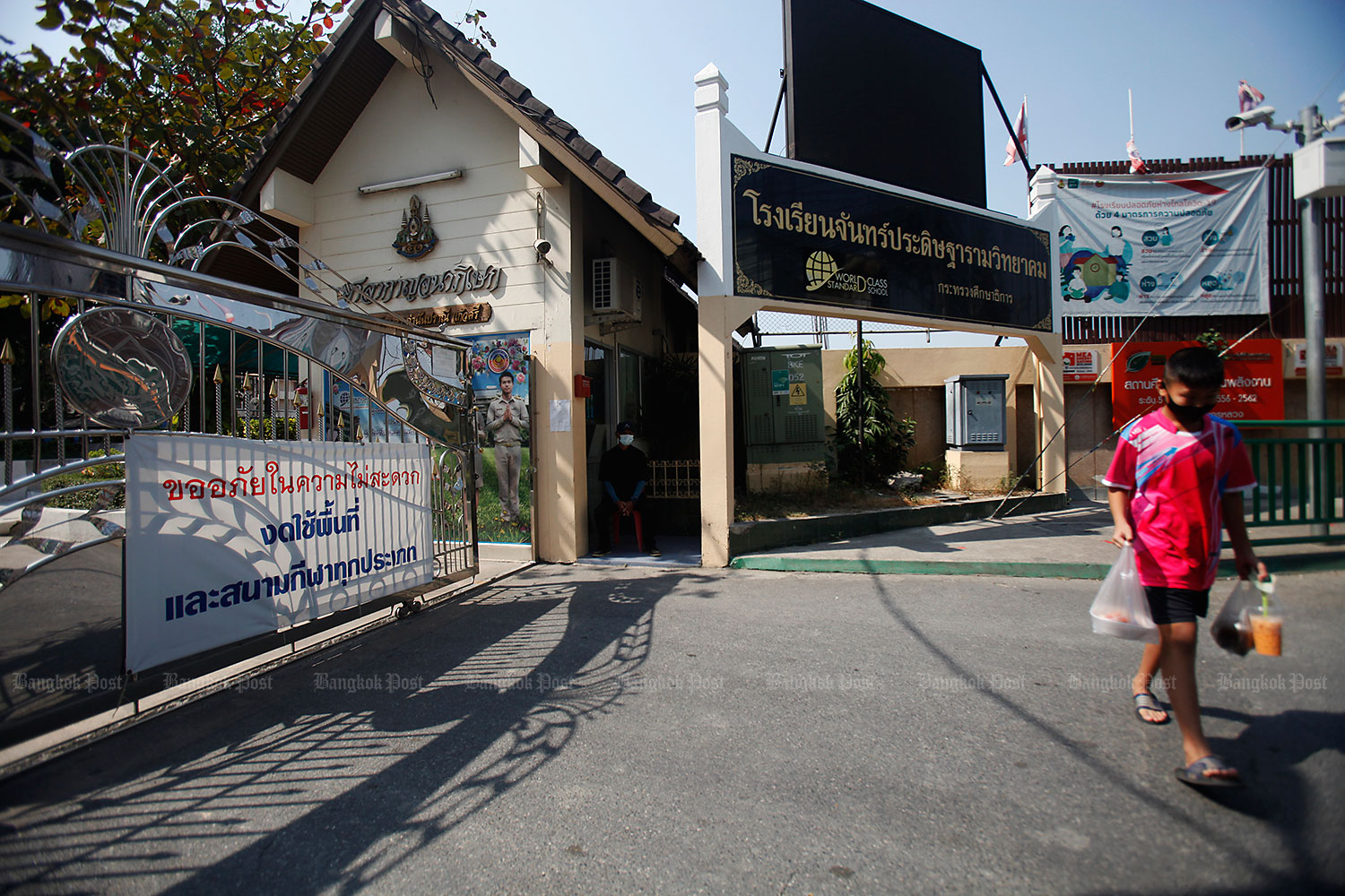 School's out ... again: A boy walks past a sign announcing Chanpradittharam Witthayakhom School in Phasi Charoen district is closed. The school suspended classes after a worker in a nearby factory contracted Covid-19. (Photo by Nutthawat Wicheanbut)