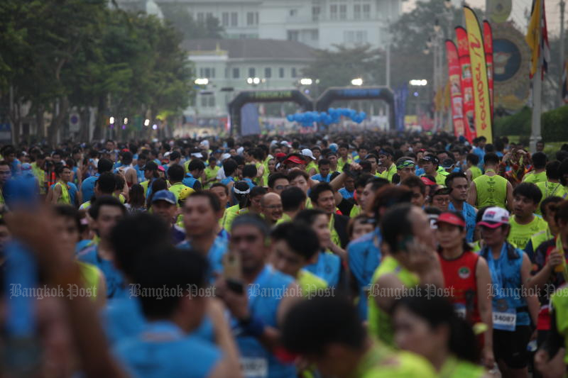 Runners wearing masks as protection against the toxic smog and coronavirus participate in the Amazing Thailand Marathon Bangkok 2020 in front of City Hall. (Photo by Apichart Jinakul)