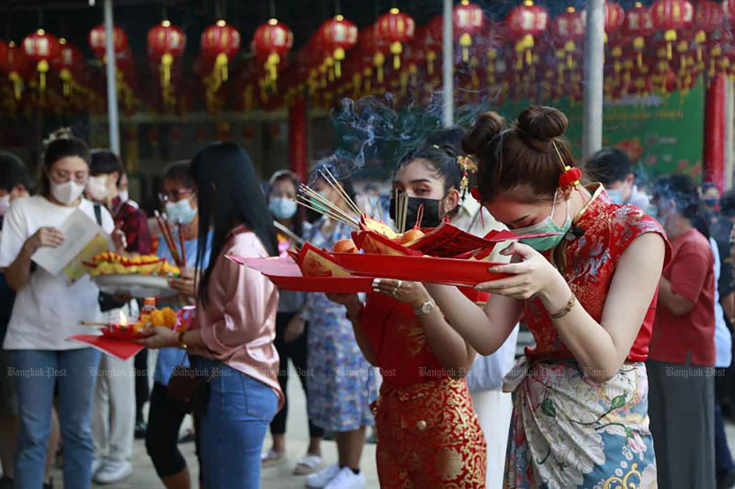 Worshippers wear the required face masks to protect against spreading Covid-19 while presenting offerings at Wat Mangkon Kamalawat in Bangkok on Thursday. (Photo: Arnun Chonmahatrakool)
