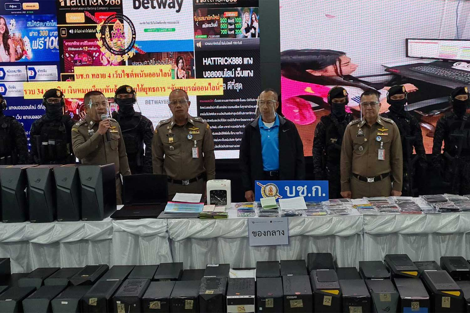 Police display the 69 computers and other evidence seized during raids on four converted shipping containers housing online gambling operations in Chanthaburi's Pong Nam Ron district, at a media briefing on Friday. (Photo: Wassayos Ngamkham)