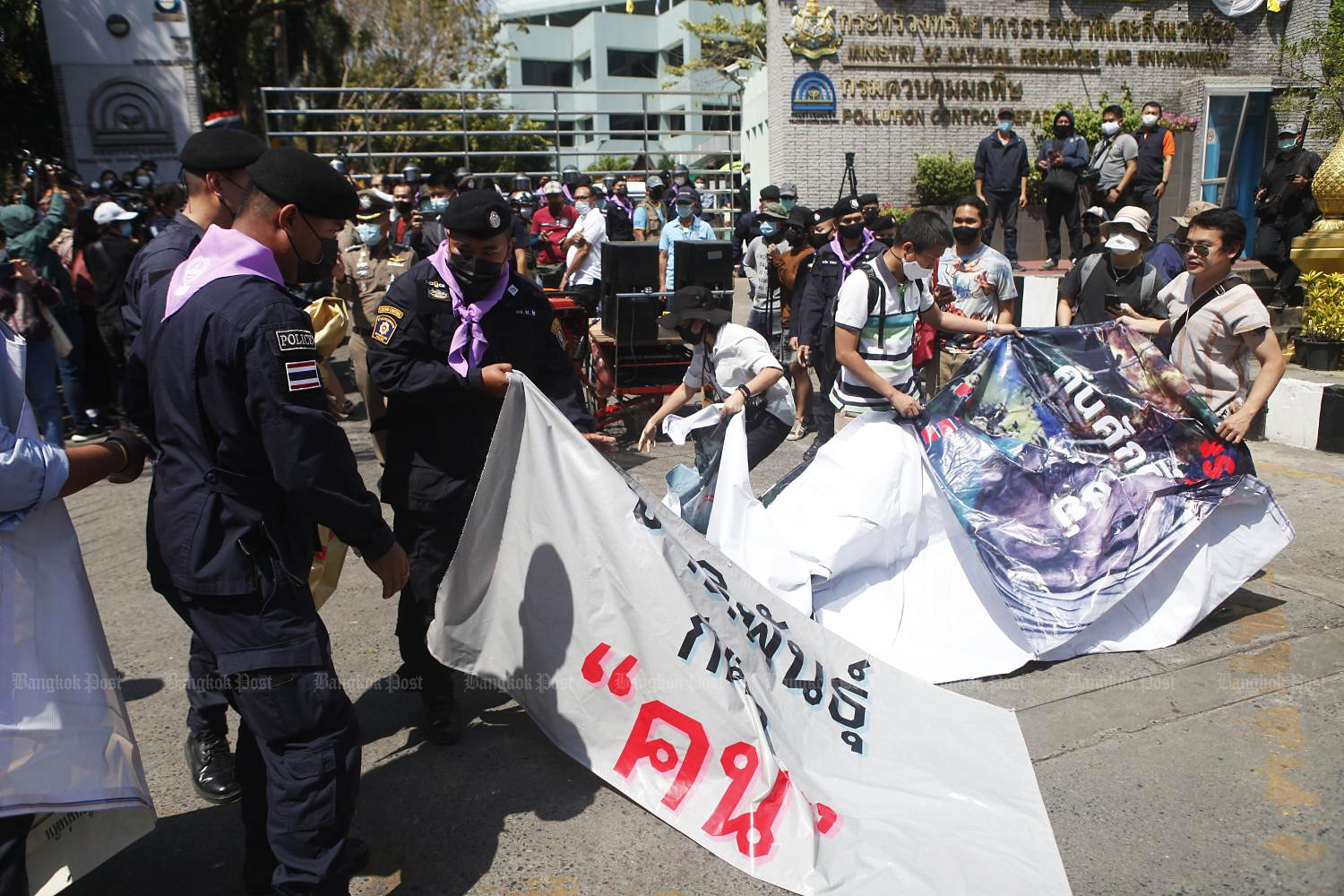 Police seize a banner from activists outside the Natural Resources and Environment Ministry on Friday during a protest against the eviction of ethnic Karen villagers. (Photo by Nutthawat Wicheanbut)