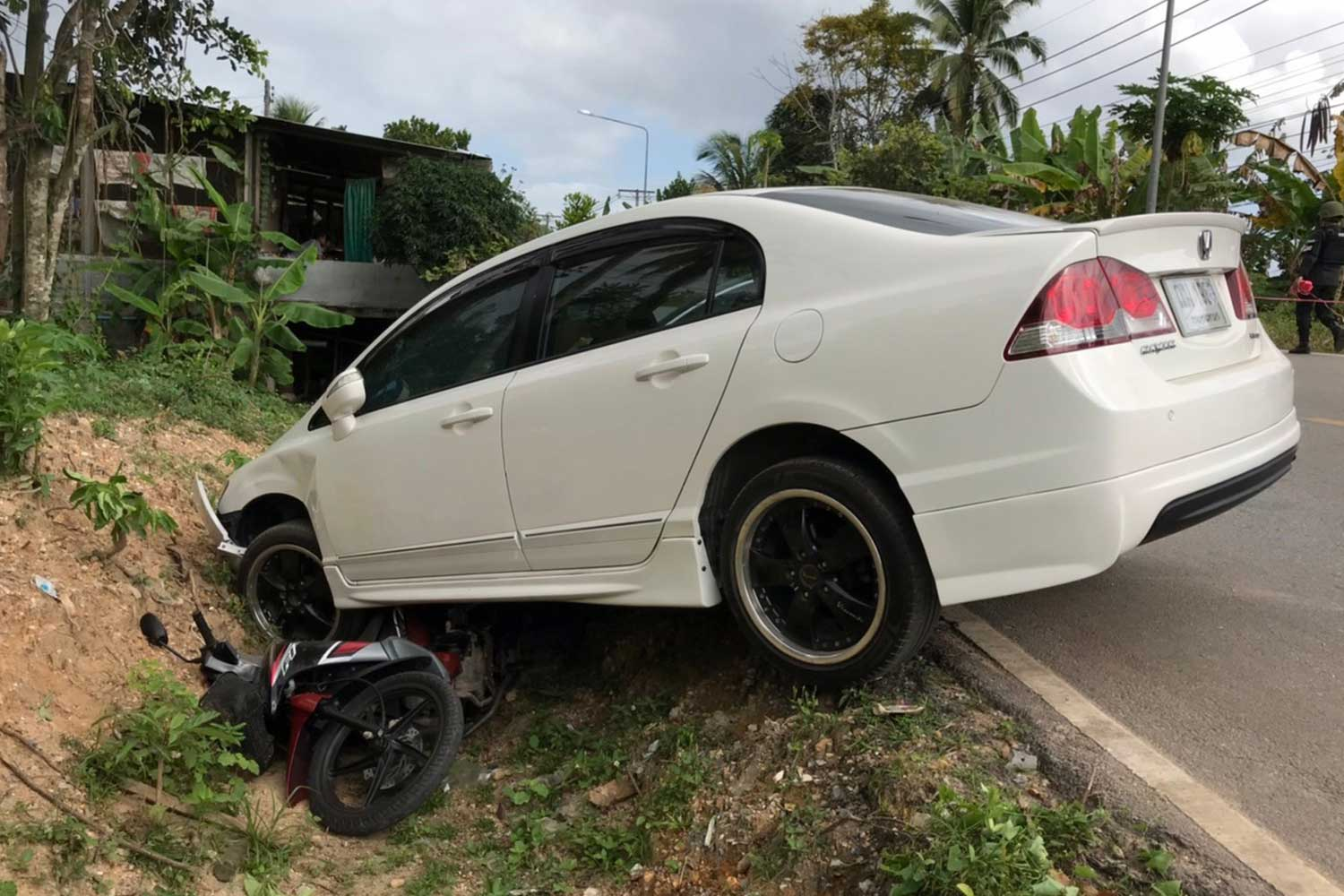 A car is found on a roadside ditch with a motorcycle of two assailants stuck underneath following a shooting attack on the driver in Thung Yang Daeng district, Pattani on Saturday morning. The assailants managed to flee on a stolen motorcycle. (Photo: Abdullah Benjakat)