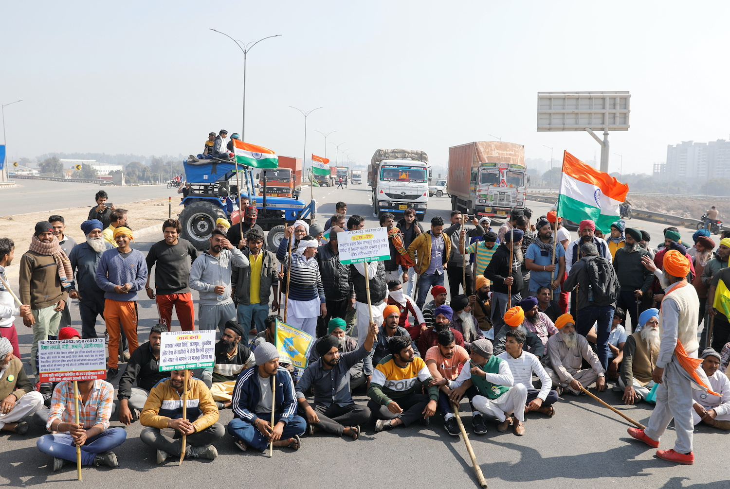 "Farmers take part in a three-hour ""chakka jam"" or road blockade, as part of their protests against farm laws on a highway on the outskirts of New Delhi on Saturday. (Reuters Photo)"