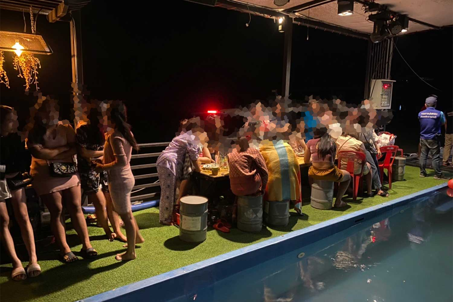 Some of the 53 young people found partying on a disco raft wait to be questioned and tested after the raft was brought ashore in Kanchanaburi province on Friday night. (Supplied photo via Piyarat Chongcharoen)