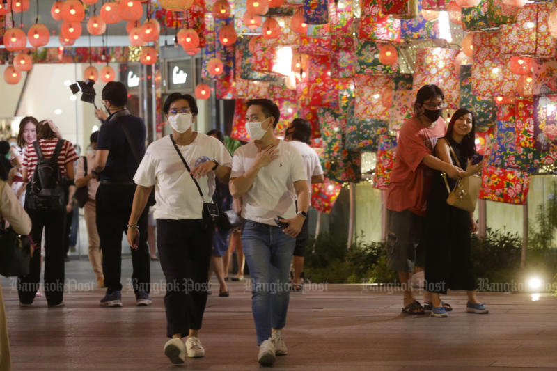 Shoppers wearing face masks walk at the EmQuartier shopping centre on Friday ahead of Chinese New Year. (Photo by Pormphom Satrabhaya)