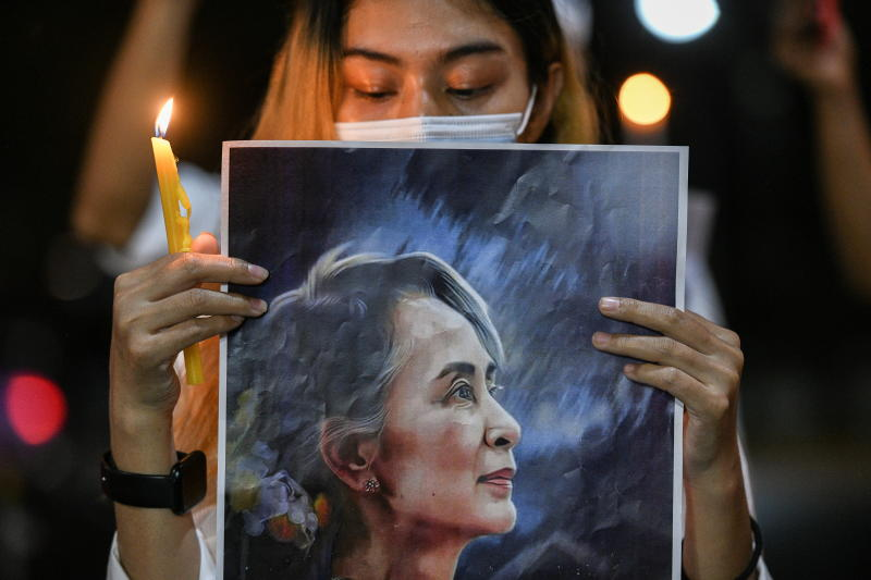 A woman holds a candle and a picture of leader Aung San Suu Kyi as Myanmar citizens protest against the military coup in Myanmar outside the United Nations venue in Bangkok on Saturday. (Reuters photo)
