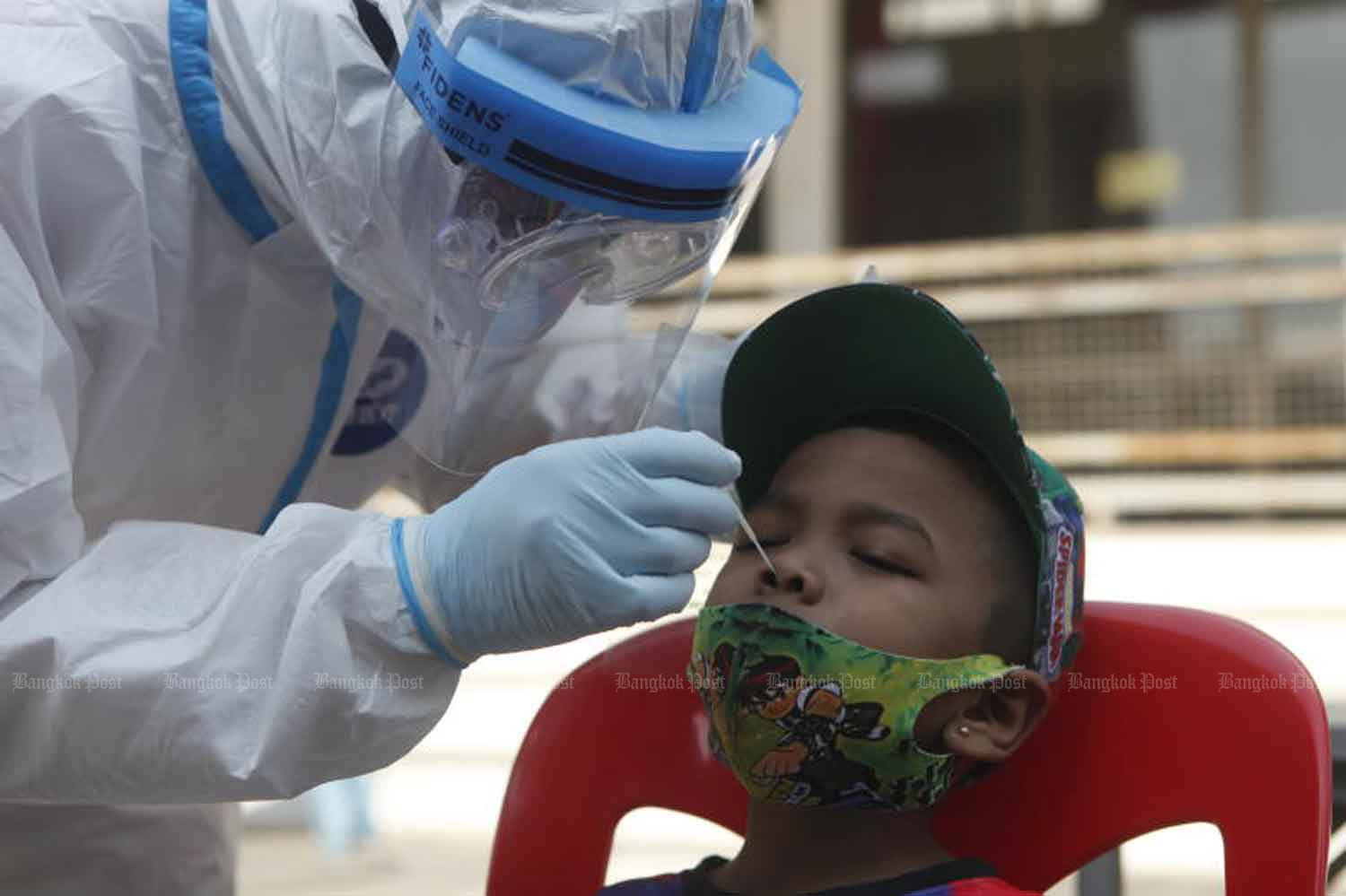 A disease control worker collects a nasal swab from a boy during active Covid-19 case finding in Phasicharoen district, Bangkok, last Thursday. (Photo: Nutthawat Wicheanbut)