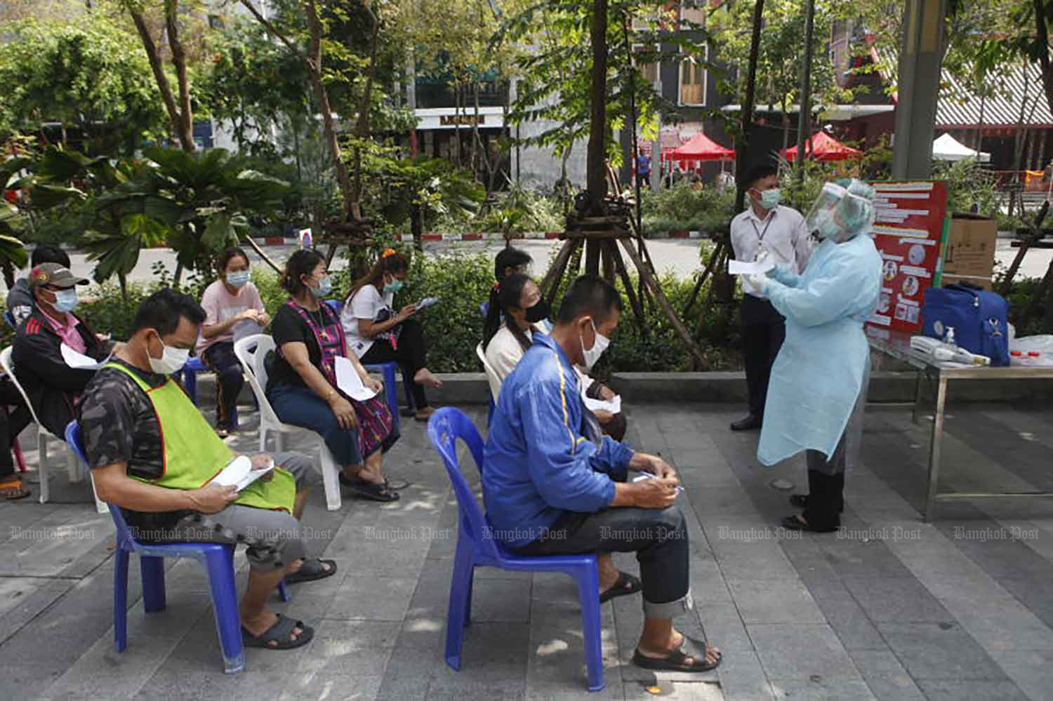 People awaiting Covid-19 tests are given a briefing by a medical officer in Suan Luang, Bangkok, on Wednesday. The tests were ordered after an infected person visited the area recently. (Photo by Nutthawat Wicheanbut)