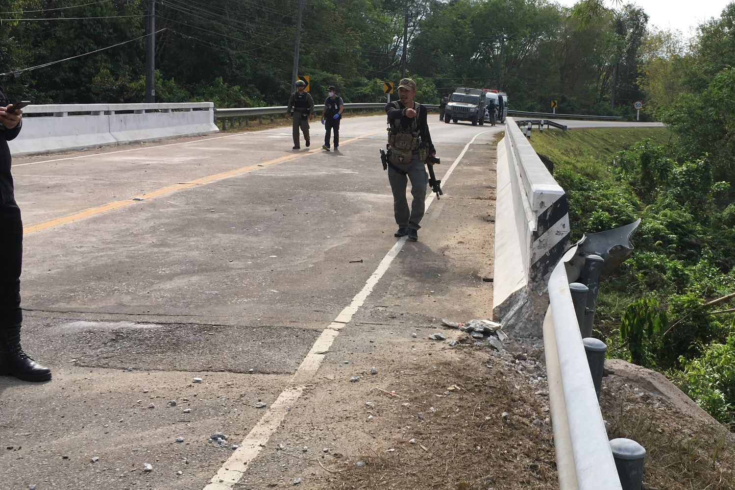 Police and explosive ordnance disposal officials check the bombing scene near a bridge in Rangae district, Narathiwat province on Saturday. (Photo by Abdullah Benjakat)