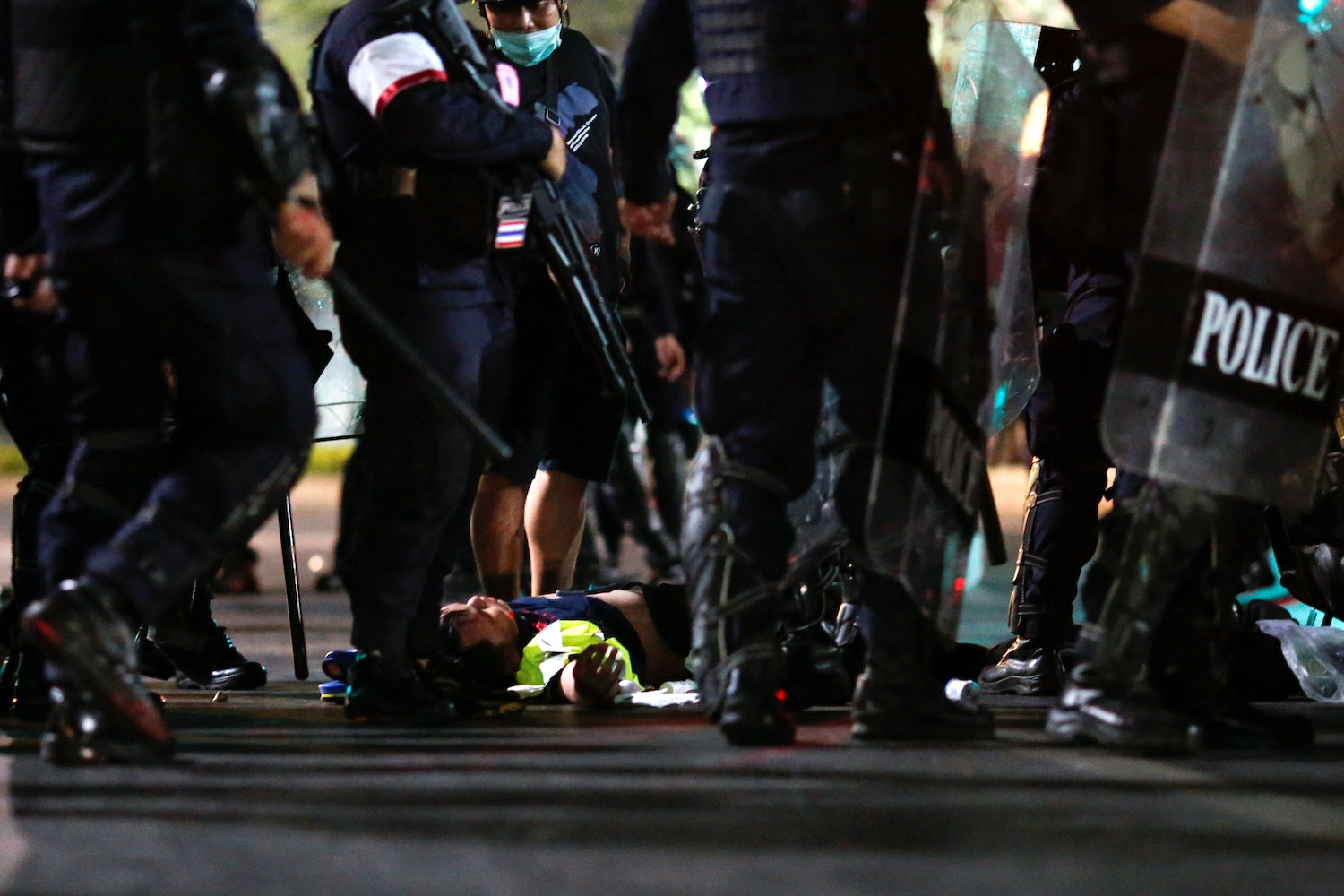 A protester lies on the ground after witnesses said he was beaten by police near Sanam Luang on Saturday night. (Reuters Photo)