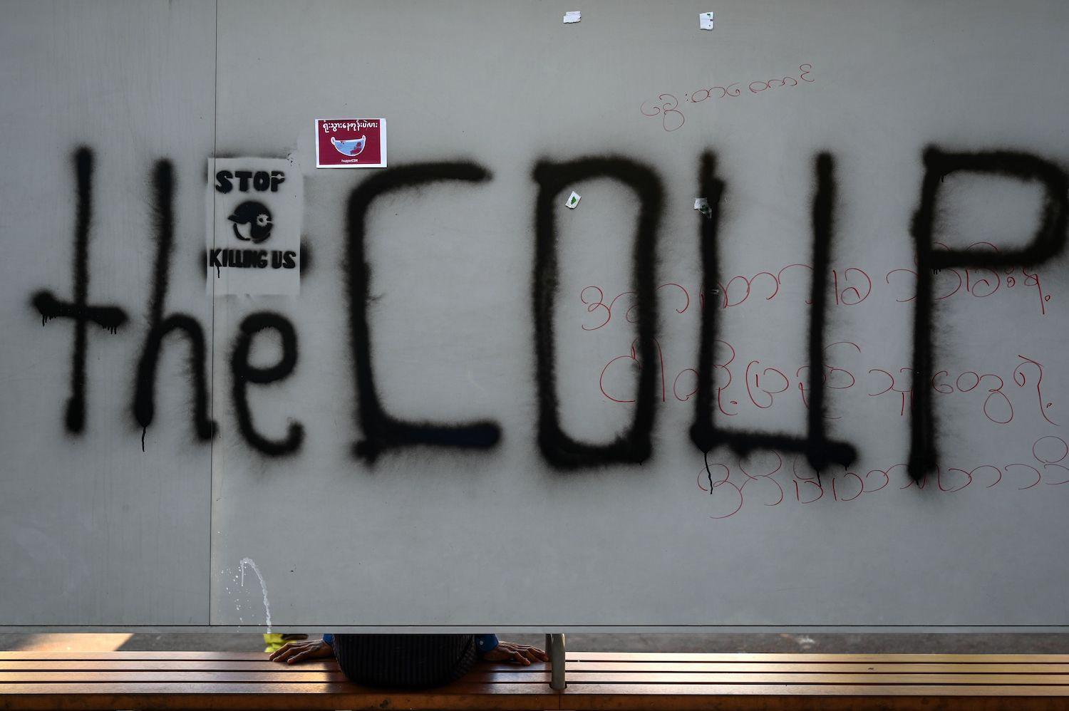 Graffiti on a bus stop in Yangon on Saturday uses a word the military doesn't like. (AFP Photos)