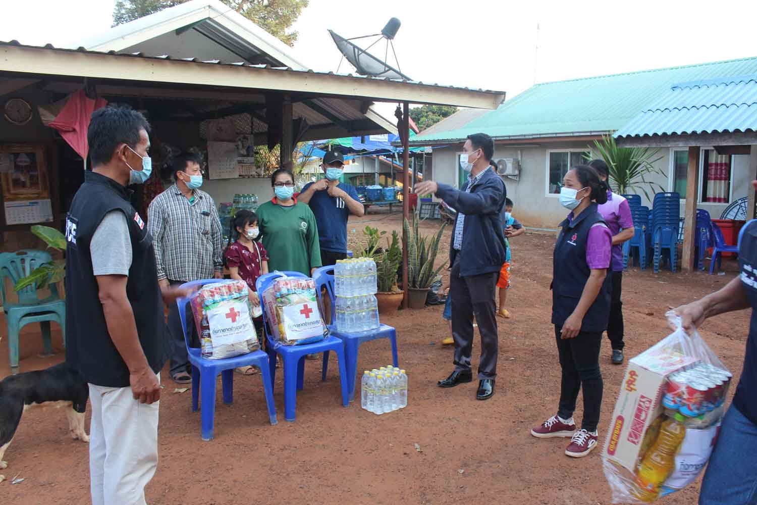 Soeng Sang district officials distribute bags of necessities to residents of Moo 7 and Moo 14 villages in tambon Kut Bot, which were locked down after a 7-year-old boy visiting from Pathum Thani tested positive for Covid-19. (Photo: Prasit Tangprasert)