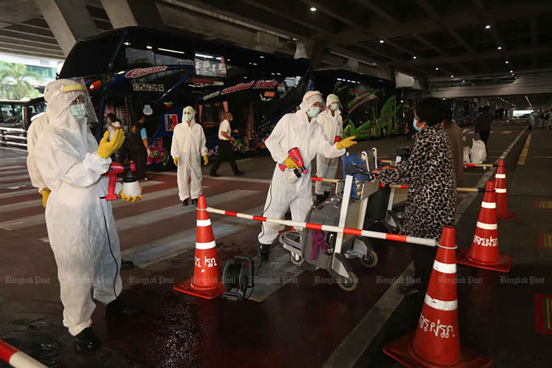 Disease control workers receive arrivals for quarantine at Suvarnabhumi airport in Samut Prakan province last October. (Photo by Arnun Chonmahatrakool)