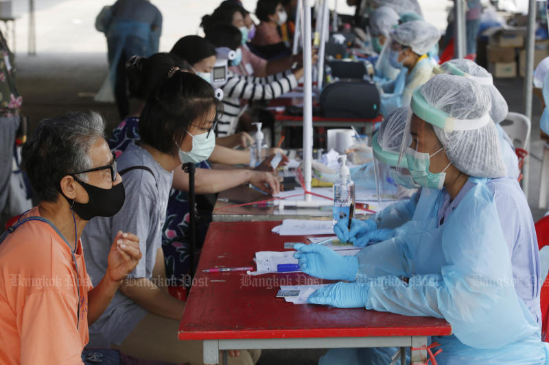 People answer questions from medics as they prepare to take a Covid-19 test at Pornpat fresh market in Pathum Thani on Sunday. (Bangkok Post photo)