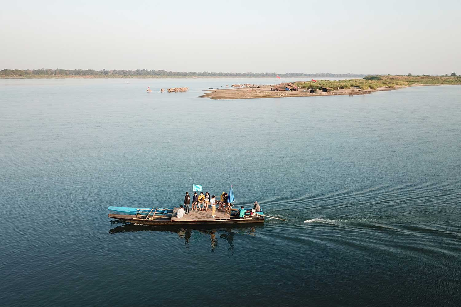 A boat leaves the Mekong River bank, taking visitors to sand beach, Had Hae (top right), in the Mekong River, in tambon Nam Kam of That Phanom district, Nakhon Phanom province. The popular island reopened to visitors last week, with strict Covid-19 controls. (Photo: Pattanapong Sripiachai)