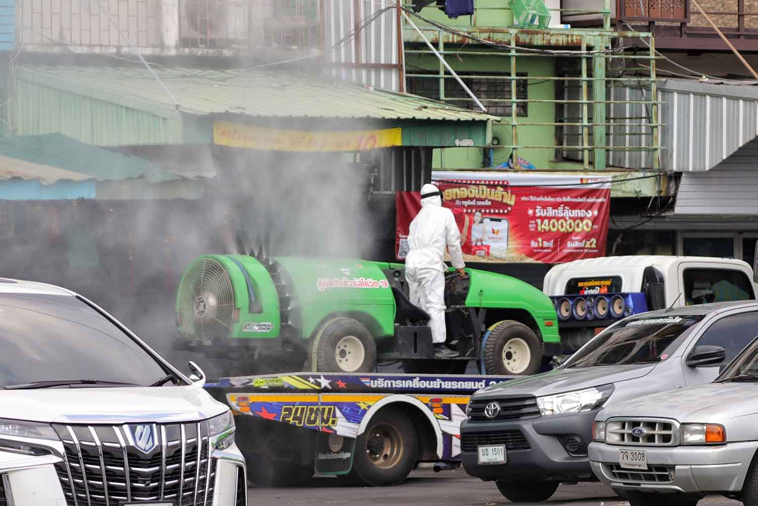 Disease control workers spray disinfectant in the vicinity of Pornpat market in Thanyaburi district, Pathum Thani, on Tuesday. (Photo: Pongpat Wongyala)