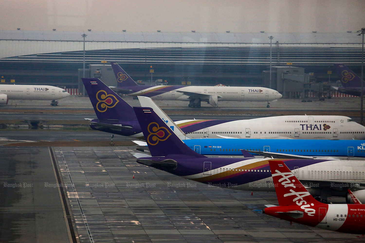 Aircraft of Thai AirAsia and Thai Airways International are parked at Suvarnabhumi airport. The Civil Aviation Authority of Thailand reported that number of domestic passengers stumbled 27.1% year-on-year in the fourth quarter, while international flights dropped by 99.1% during the period. (Photo by Wichan Charoenkiatpakul)
