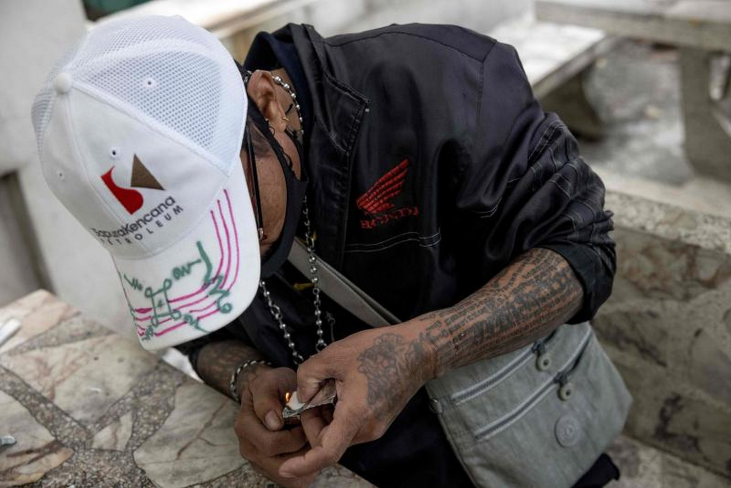 Motorbike taxi diver Soonthorn poses for photos as he demonstrates how he smokes a methamphetamine pill, during an interview with AFP in Bangkok. (Photo: Jack Taylor/AFP)