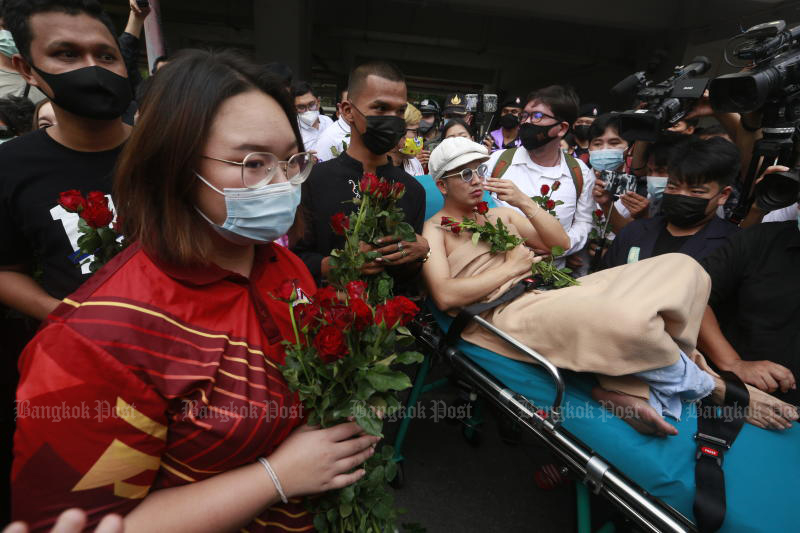 Panusaya Sithijirawattanakul (left) and other protest leaders receive roses from supporters as they arrive at the Office of the Attorney-General, where public prosecutors submitted evidence supporting charges against them, on Wednesday. (Photo by Arnun Chonmahatrakool)