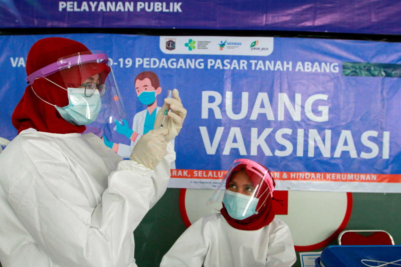 A health care worker prepares a dose of China's Sinovac Biotech vaccine for the coronavirus disease (Covid-19), during mass vaccination for vendors at the Tanah Abang textile market in Jakarta, Indonesia on Wednesday. (Reuters photo)