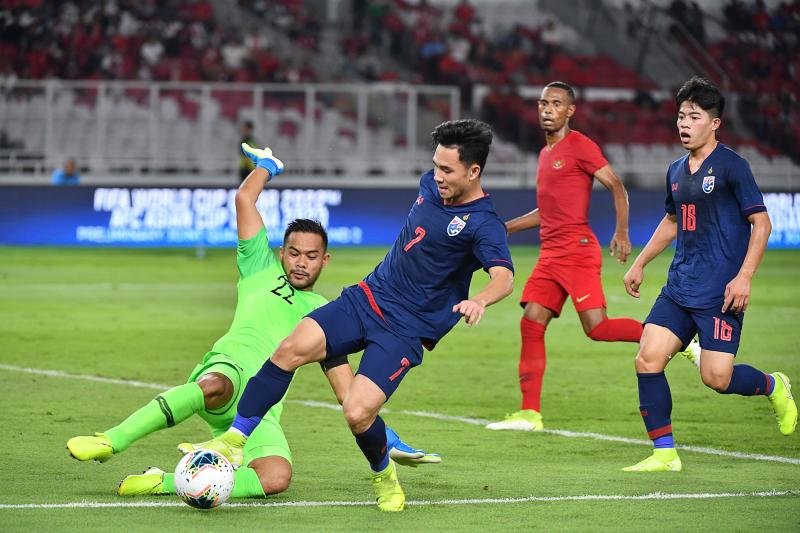 FILE PHOTO: Supachok Sarachat (#7) of Thailand vies for a ball with Indonesian goal keeper Andritany Ardhiyasa during the second round Group G qualification football match for the 2022 Qatar FIFA World Cup between Indonesia and Thailand at Gelora Bung Karno Stadium in Jakarta on Sept 10, 2019. (AFP)