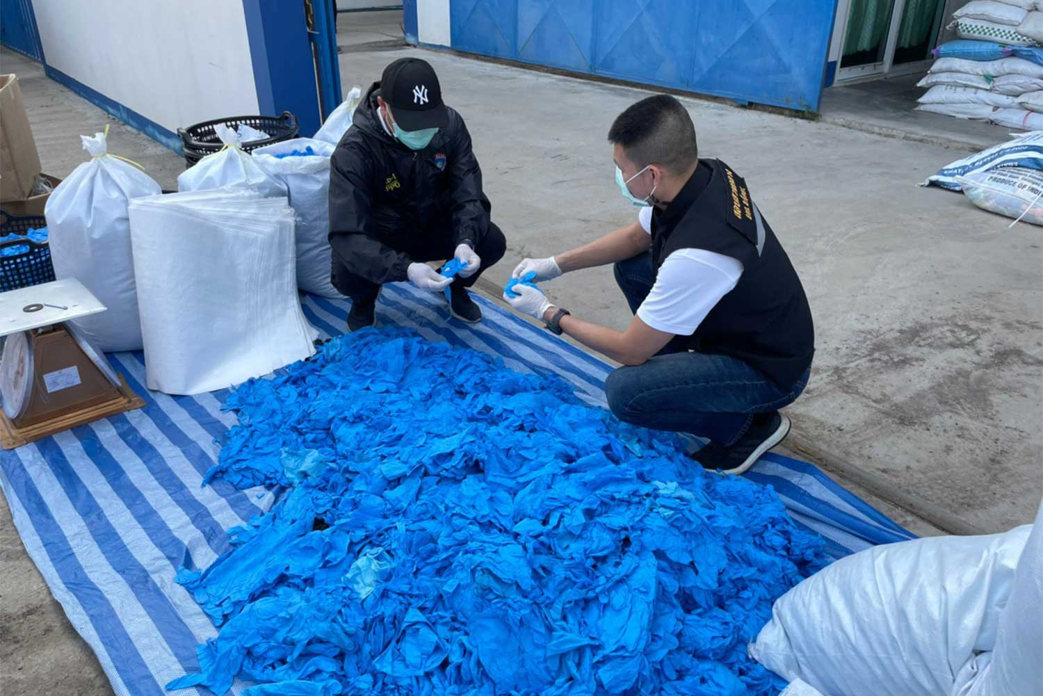 Police examine used gloves which were washed and ready for packing for resale, at a  warehouse in Lat Lum Kaeo district, Pathum Thani province, on Wednesday. About 37 tonnes of gloves were seized, worth about 6 million baht. (Photo supplied/Wassayos Ngamkham)