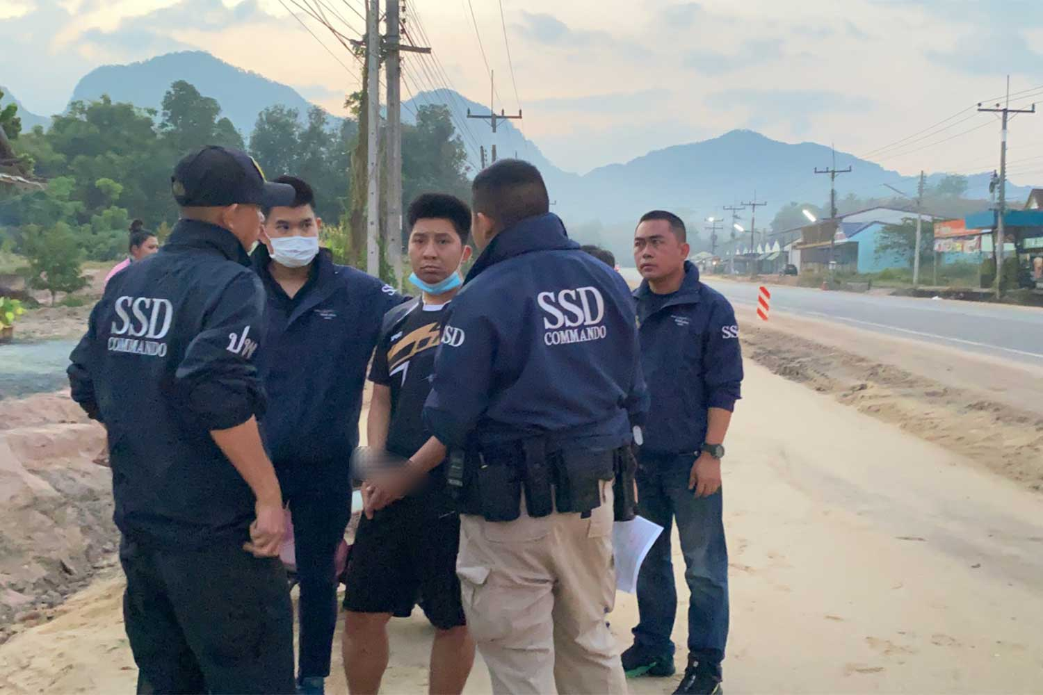 Jakkrawut Yimphat, 26, a national park employee, face mask under his chin, is taken from his house in Surat Thani by police commandos. He is charged with fooling a 16-year-old girl to pose nude for videos, and then extorting her. (Photo supplied/Wassayos Ngamkham)