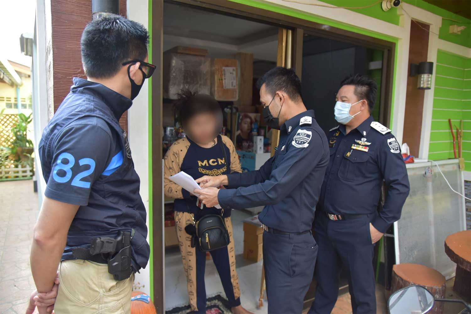 Department of Special Investigation officers show their search warrant to the wife of  Charanin Muenchit, also known as Theerathat Thornkanok, as they arrive to search his house in Sukhothai on Thursday morning. (Photo from @DSI2002 Facebook page)