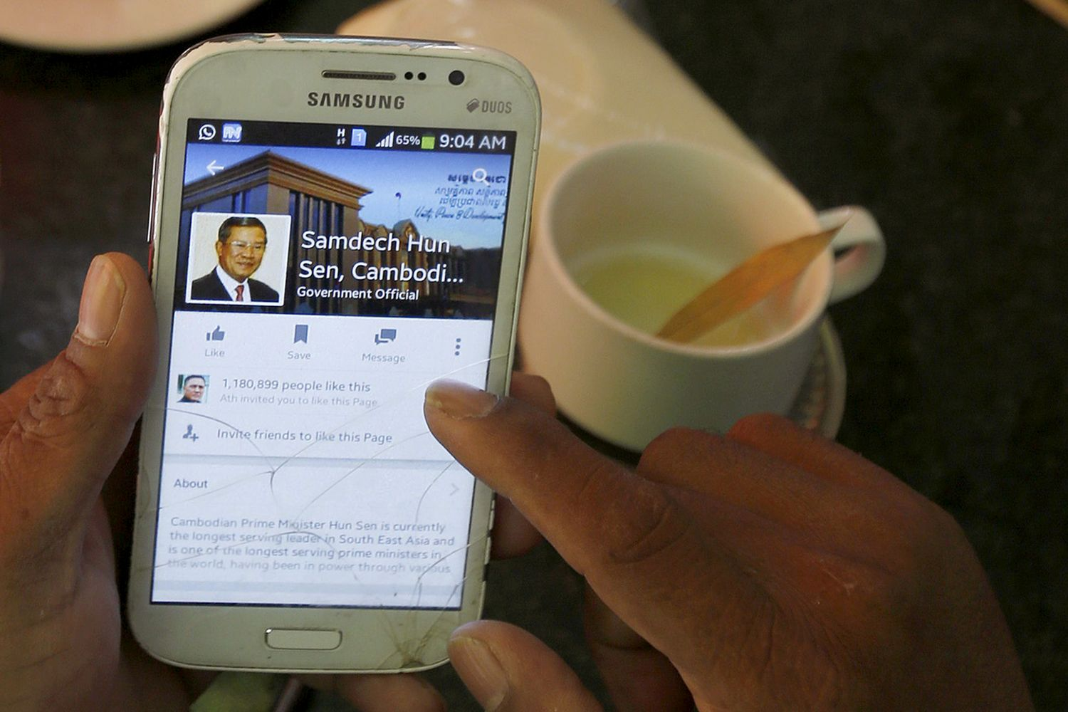 A person uses a smartphone to look at the Facebook page of Cambodia's Prime Minister Hun Sen, during breakfast at a restaurant in central Phnom Penh on Oct 7, 2015. (Reuters photo)