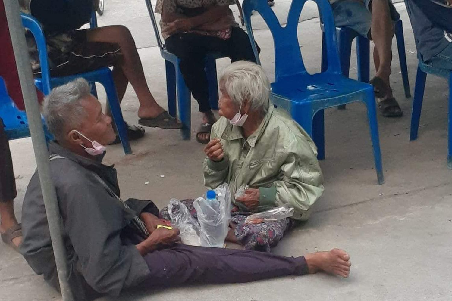 Noi Aiamsaart (right), 81, and her son Chamnian, 62, residents of Kamphaeng Phet, have lunch while waiting to register for the Rao Chana programme, which gives 7,000 baht each to eligible people to help cope with Covid-19 hardships in front of Krungthai Bank's Tha Makua branch in Kamphaeng Phet province on Tuesday. (Photo from 