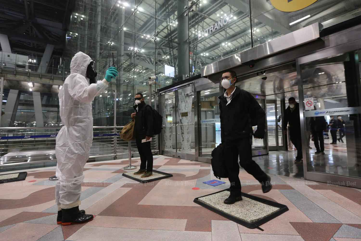 A healthcare worker thoroughly screen passengers upon arrival at Suvarnabhumi airport amid the Covid-19 pandemic. (Photo by Wichan Charoenkiatpakul)
