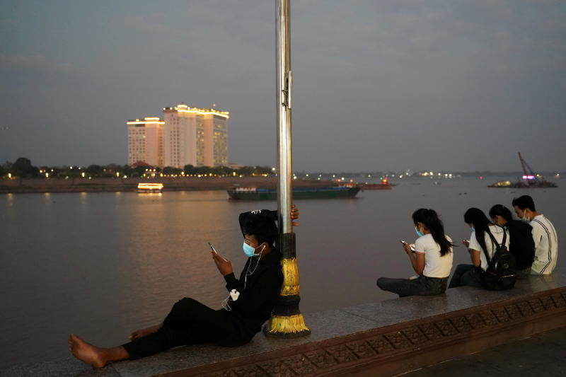 People uses their mobile phones on the Tonle Sap riverside in Phnom Penh on Thursday. (Reuters photo)