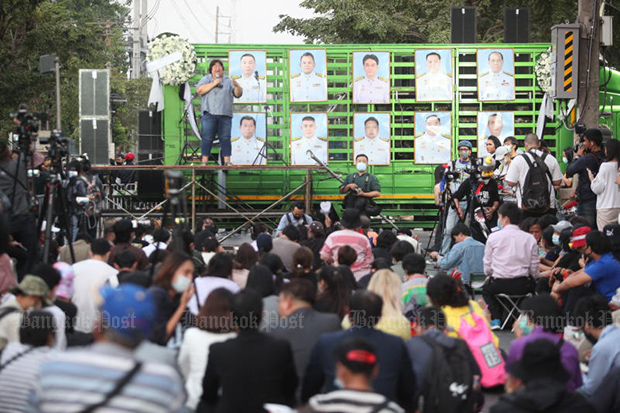 Protesters listen to a speaker on a stage in front of pictures of nine ministers being grilled in and outside Parliament on Friday. (Photo by Pattarapong Chatpattarasill)
