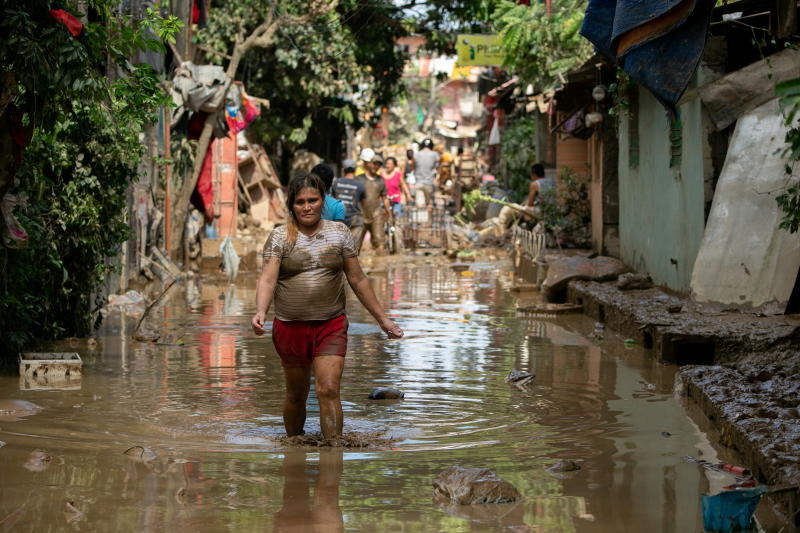 FILE PHOTO: A woman wades through muddy floodwater following Typhoon Vamco, in San Mateo, Rizal province, Philippines, Nov 13, 2020. (Reuters)