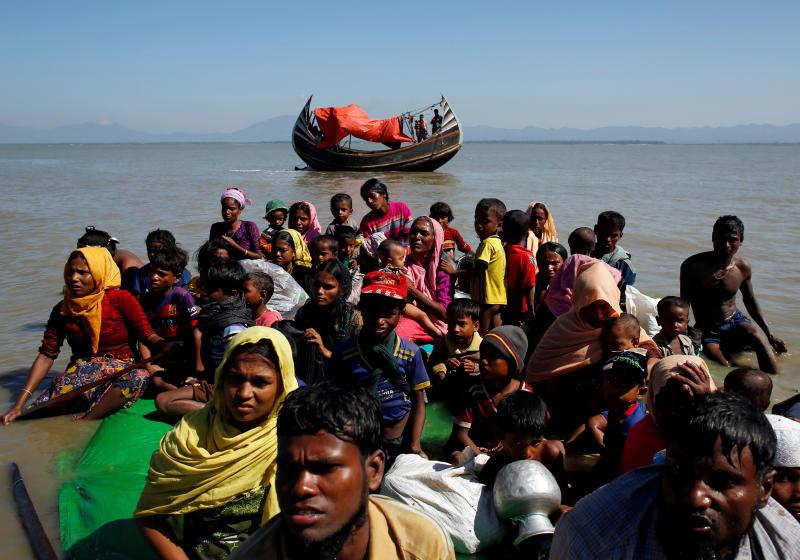FILE PHOTO: Rohingya refugees sit on a makeshift boat as they get interrogated by the Border Guard Bangladesh after crossing the Bangladesh-Myanmar border, at Shah Porir Dwip near Cox's Bazar, Bangladesh Nov 9, 2017. (Reuters)