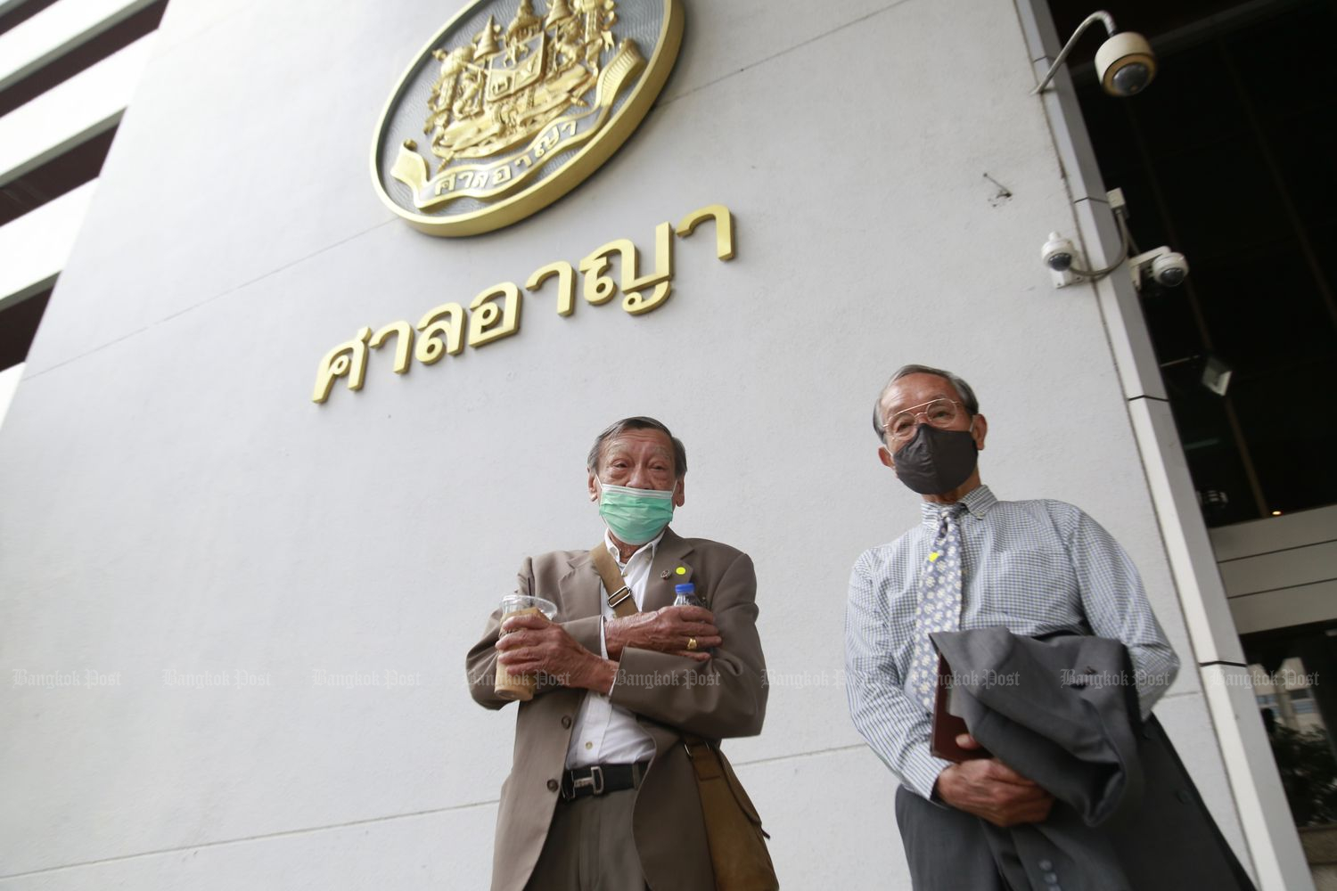 Panas Tassaneeyanon (left), a former rector of Thammasat University's Faculty of Law, and Charnvit Kasetsiri, an ex-dean of the university, arrive at the Criminal Court on Monday to offer themselves as guarantors for four Ratsadon co-leaders held on lese majeste charges since Feb 9. (Photo by Arnun Chonmahatrakool)