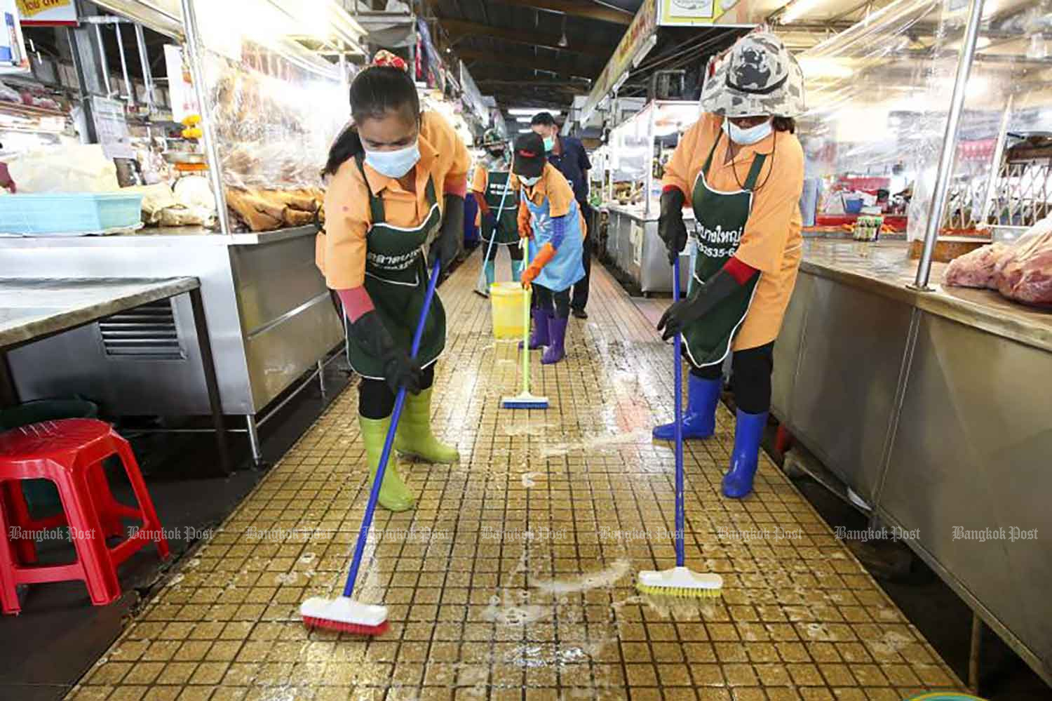 Workers clean the floor of Bang Yai market in Bang Yai district, Nonthaburi, in a bid to control the spread of Covid-19 on Tuesday when 95 new Covid-19 cases were reported in the country. (Photo by Pattarapong Chatpattarasill)