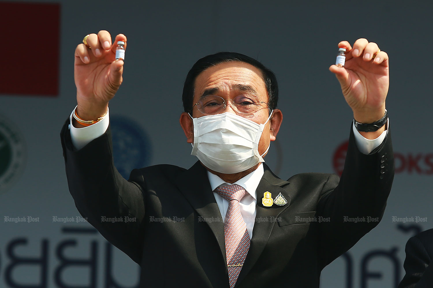 Prime Minister Prayut Chan-o-cha holds up two vials as he announced the arrival of the first batch of a Covid vaccine from China on Wednesday. (Photo by Somchai Poomlard)
