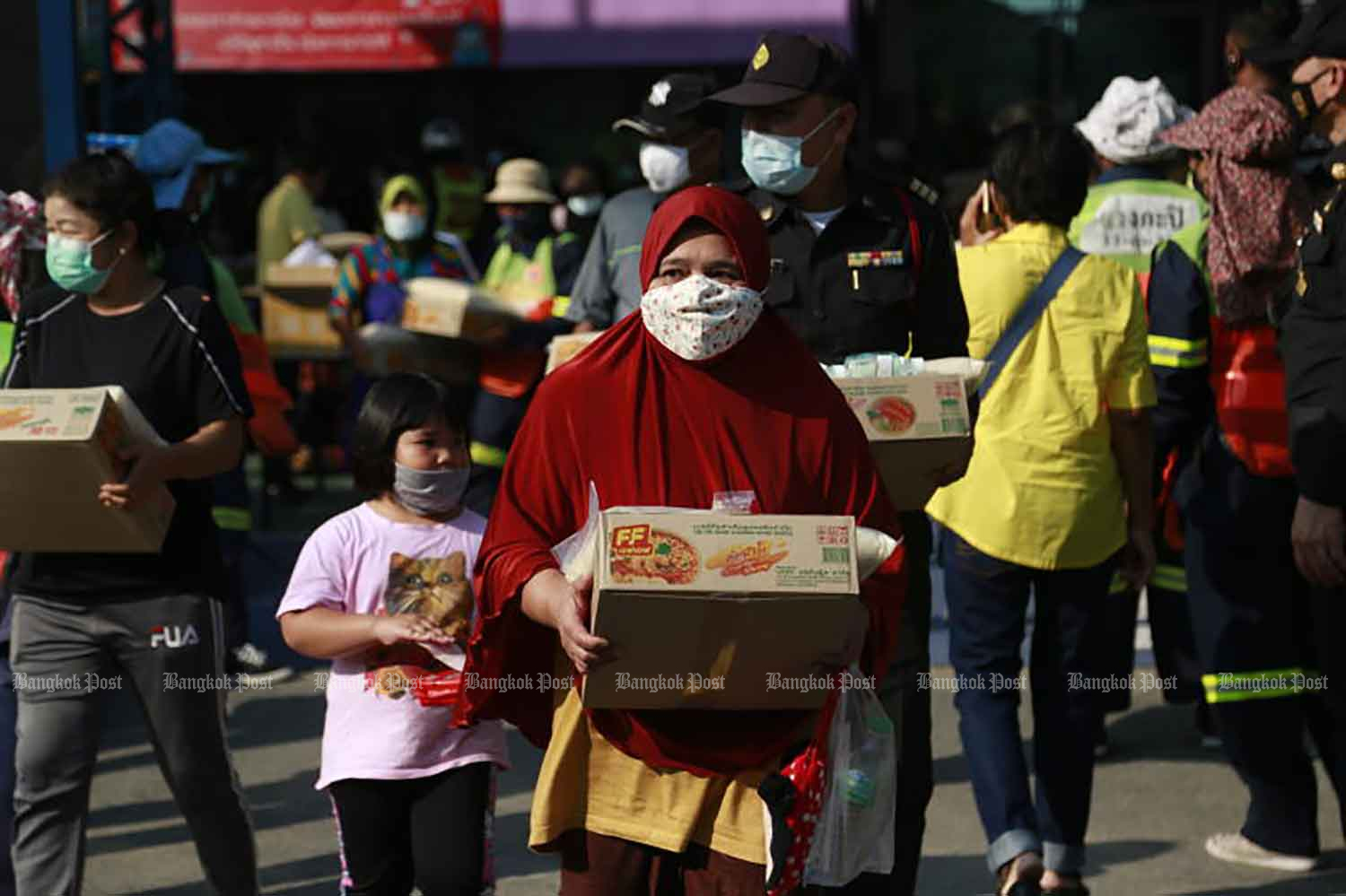 People receive food handouts in the wake of the Covid-19 pandemic at Wang Som community in Bang Kapi district, Bangkok, on Wednesday when the country confirmed 72 new Covid-19 cases. (Photo by Arnun Chonmahatrakool)