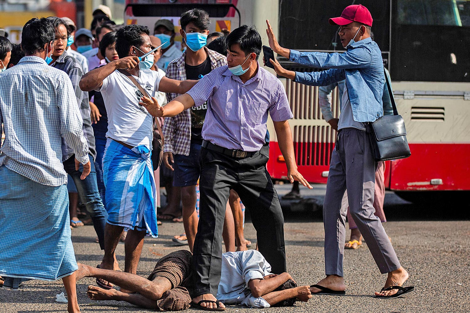 A military supporter points a knife at someone as he confronts anti-coup protesters during a pro-military rally in Yangon on Thursday.(Reuters photo)